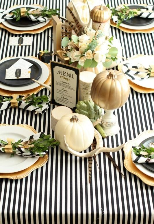 modern table setting with a striped tablecloth, natural pumpkins, antlers and feathers
