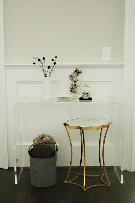 skulls in jars on a console entryway table