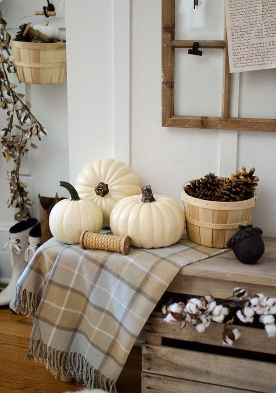 create a fall display with a neutral plaid blanket and pumpkins