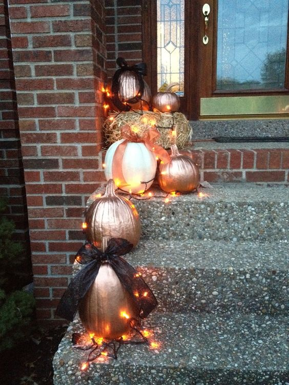 painted pumpkins outside displayed with lights