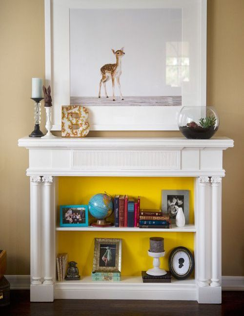 shelves inside a faux fireplace with books and decorations