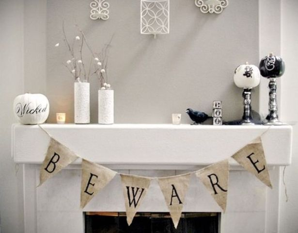 white Halloween mantel decor with a banner and several pumpkins on stands