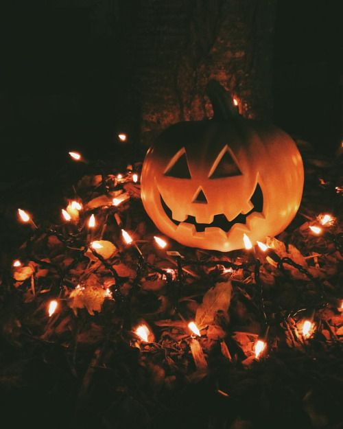 put a pumpkin on a pile of fall leaves and light it up