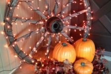 27 rustic-style decor with a large wooden wheel covered with lights