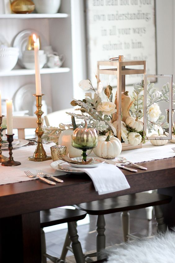 vintage-inspired table setting with candles and a pumpkin lantern