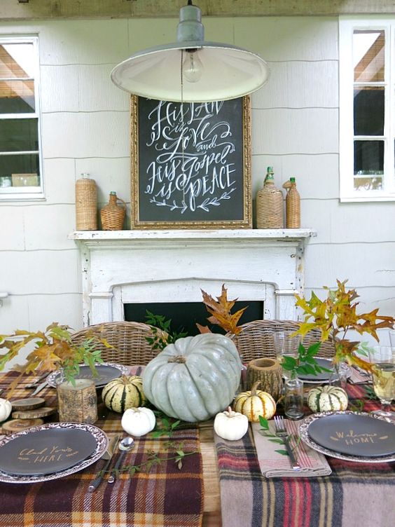 plaid tablecloth, pumpkins, leaves and gourds with black chargers
