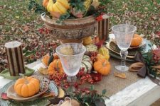 rustic tablescape with pumpkins, gourds and berries and a burlap tablecloth