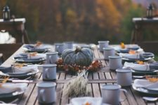 simple outdoor table with a pumpkin centerpiece and leaf napkin rings