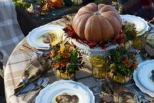 traditional table decor with a large pumpkin and fall flowers
