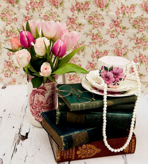 a stack of books, tulips in a vase, a vintage tea cup with pearls
