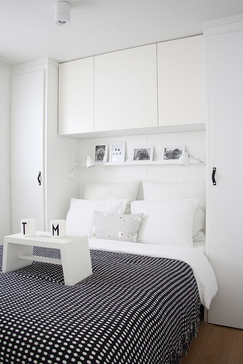 built in bed surrounding storage and a narrow shelf above the bed