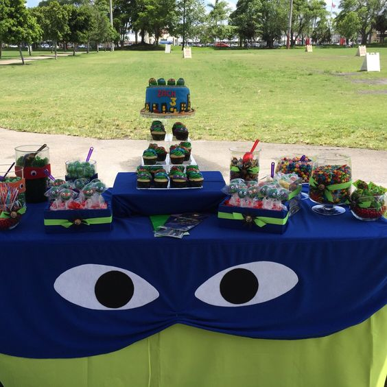 decorate candy table with a fabric mask and eyes, place a lot of colorful desserts