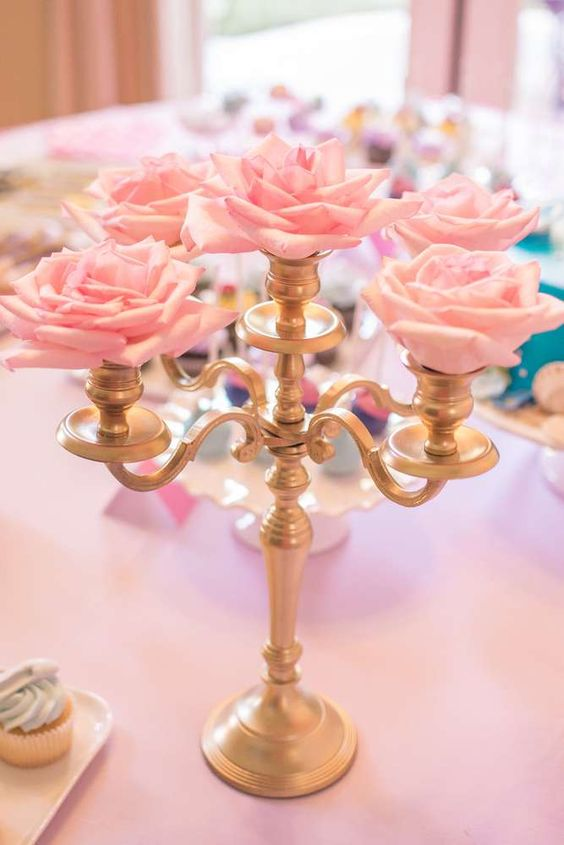 centerpiece of a gold candle holder and silk pink roses