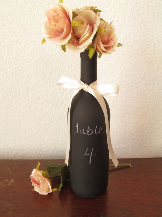 chalkboard wine bottle with white ribbon and flowers