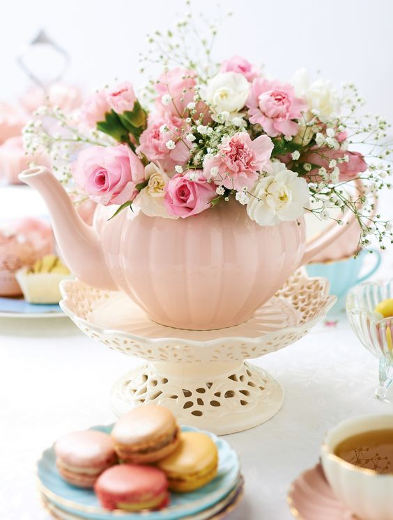 dusty pink tea pot used as a vase for the table