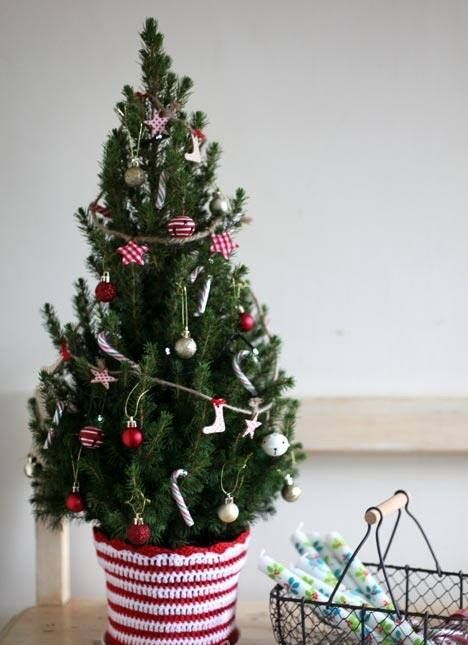 a tiny tree decorated with tiny ornaments placed in a pot with a crochet cover