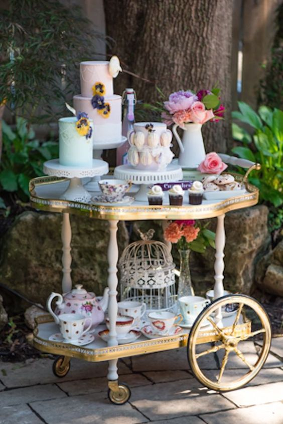 gilded tea cart, vintage cups and a tea pot, cakery with fresh flowers