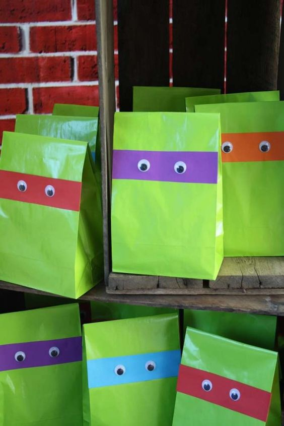 make your own paper favor bags using green paper and googly eyes