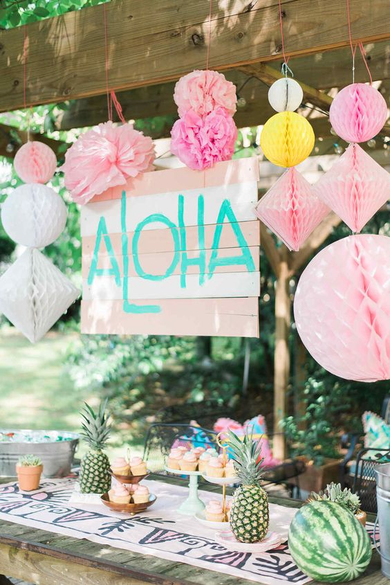 colorful paper decorations and fans, pineapples for table decor