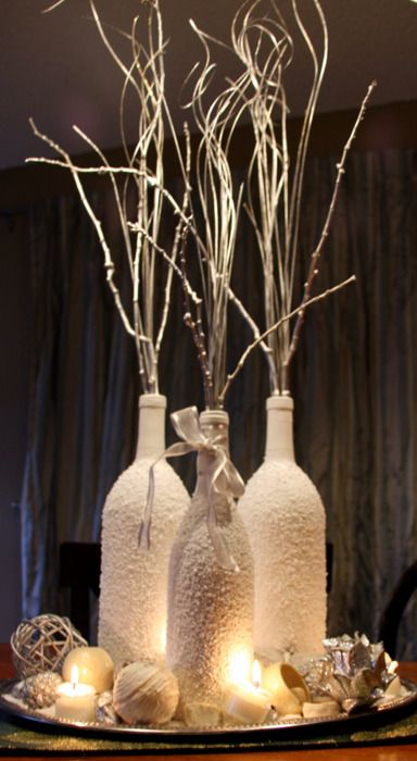 frosted wine bottles with white branches, yarn, candles and pinecones