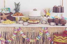 12 luau dessert table decorated with Hawaiian items and paper flowers
