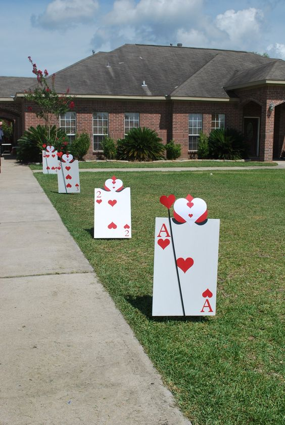 instead of balloons, oversized playing cards lining driveway for Alice In Wonderland party