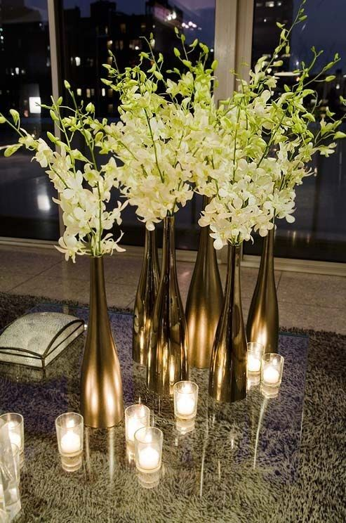Picture of metallic wine bottles and white flowers for an