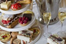 15 desserts and treats on a modern white stand and some champagne