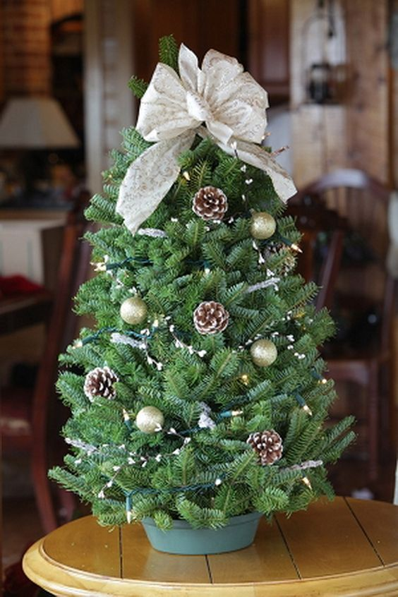 tableltop Christmas tree with a large bow, pinecones and tiny ornaments