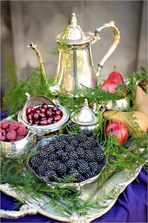 berries displayed in a silver set and surrounded with evergreens
