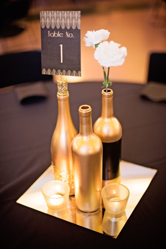 gold and glitter wine bottles with candles on a mirror