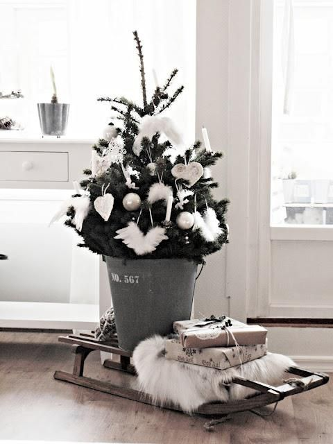 tree decorated with fluffy and just white ornaments placed into a bucket and on a
