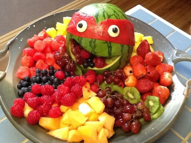 cut a watermelon and add a mask, place fruits on the dish