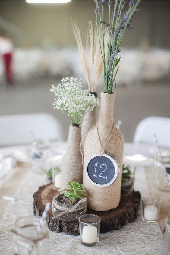 totally wrapped yarn bottles with spikes and herbs, a chalkboard table number on a wood slice