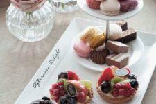 23 tarts, macarons servedon simple white tableware
