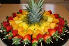 24 fruit skewers for a party, the top of a pineapple to stabilize the skewers