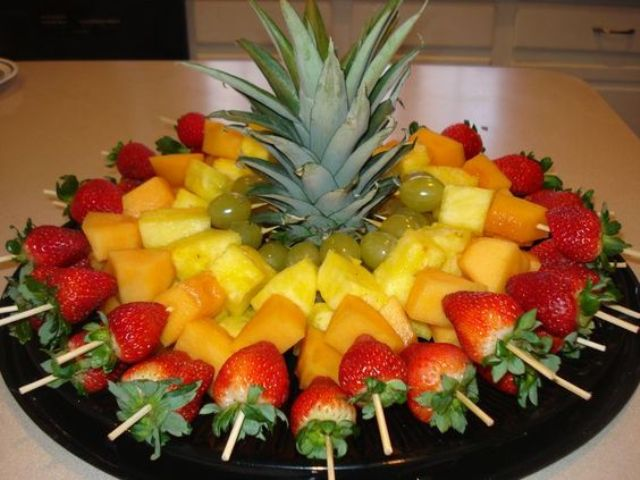 fruit skewers for a party, the top of a pineapple to stabilize the skewers