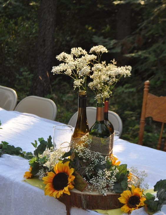 wine bottles tied together with burlap and sunflowers for a rustic centerpiece