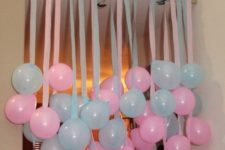 25 pink and blue balloons hanging from above is an easy way to decorate