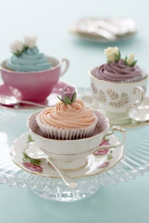 place pastel cupcakes topped with flowers into vintage tea cups to serve