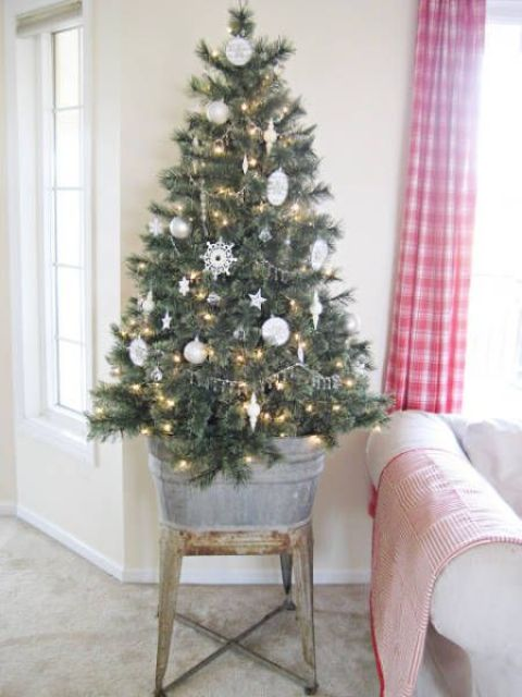 white ornaments and lights on tree placed into a bathtub