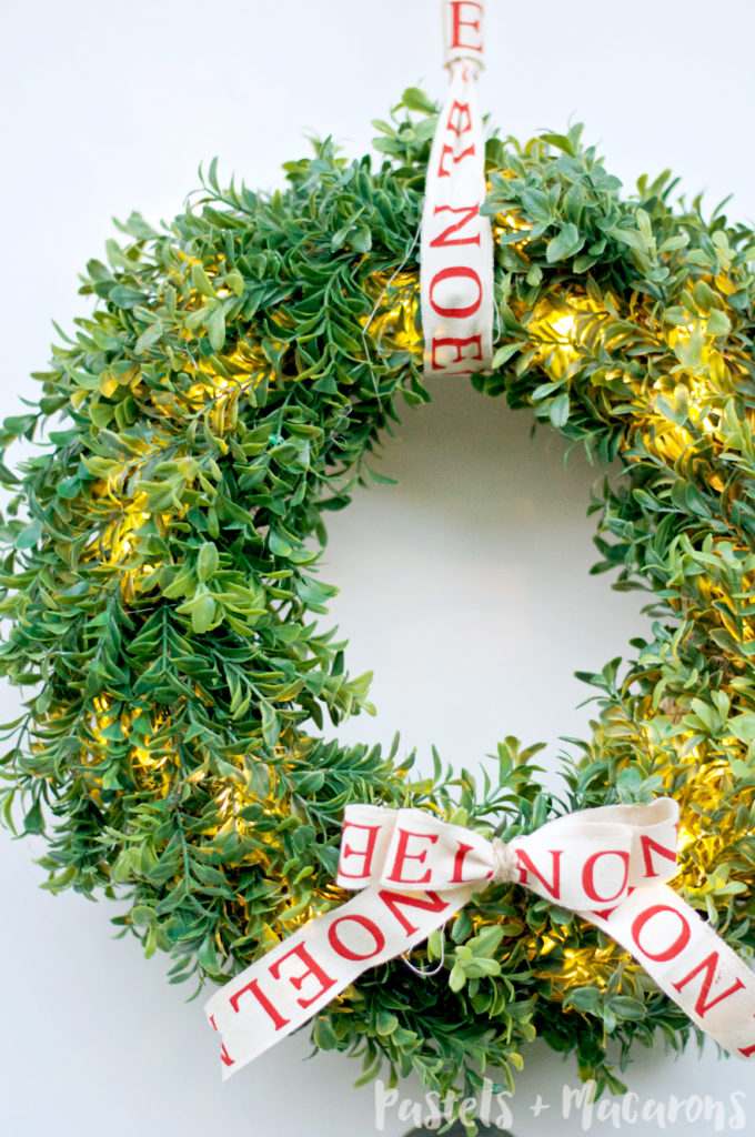DIY boxwood lit up wreath with a bow (via www.pastelsandmacarons.com)