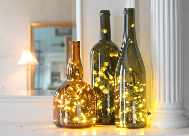 DIY wine bottle lanterns with Christmas lights (via www.ehow.com)