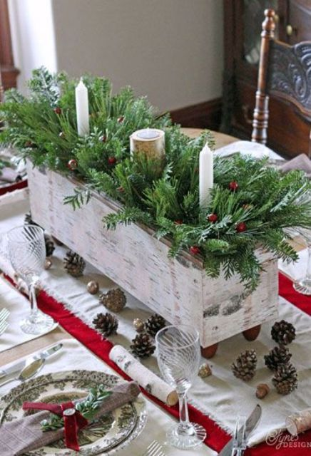 a box with evergreens, berries and candles