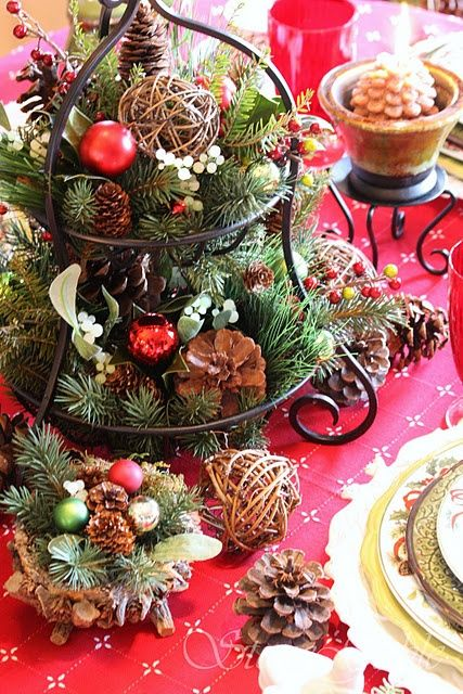 a cupcake stand with evergreens, pinecones and vine balls