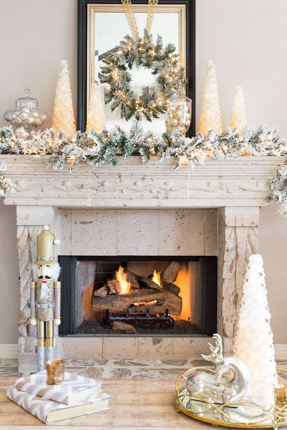 a faux snowy garland and wreath with lights - Christmas Mantel Decor