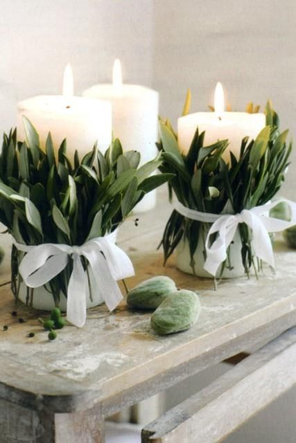 candle with leaves wrapped around it and ribbon bows looks fresh and elegant