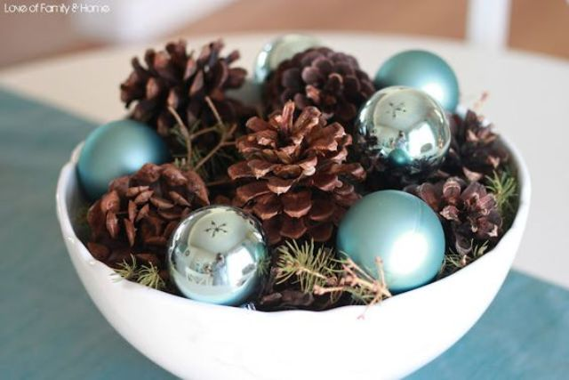 a bowl with pinecones and blue ornaments