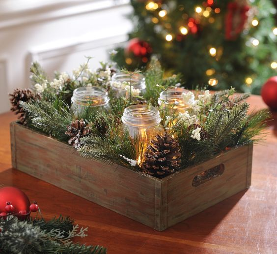 a crate with evergreens, pinecones and candles in jars