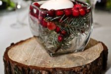 03 a wooden slice with a glass jar and evergreens, berries and a floating candle